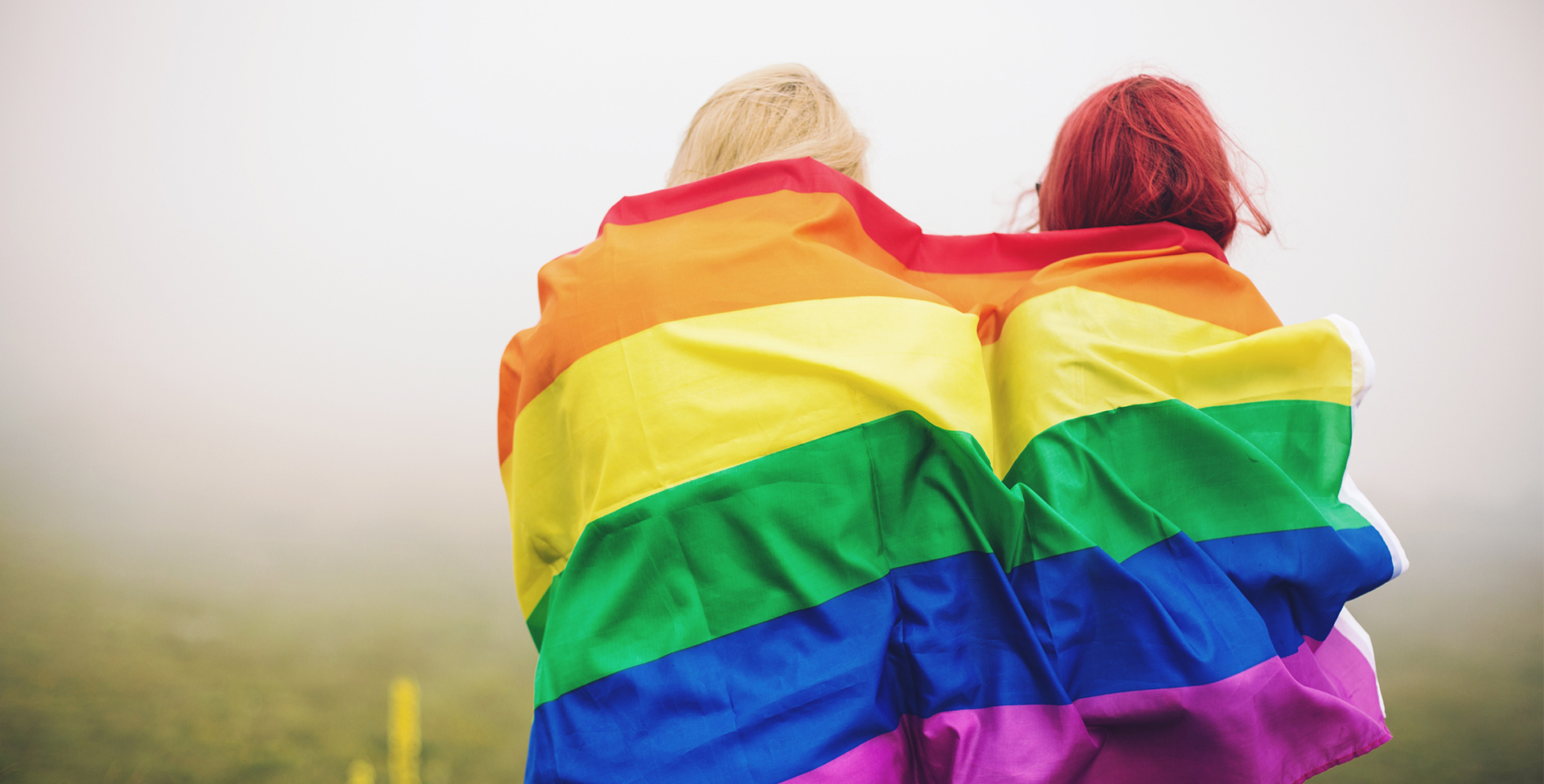 women wrapped in rainbow flag
