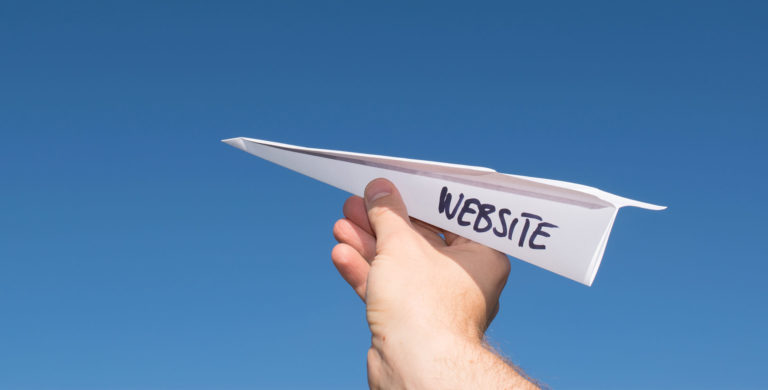 "a paper airplane with the word ""website"" written on its side"